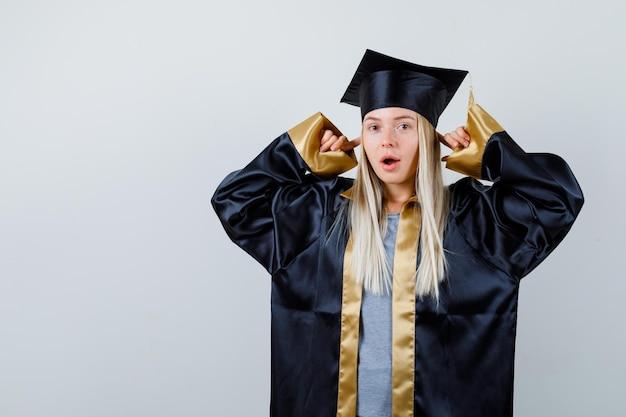Rapariga loira tapando as orelhas com o dedo indicador, usando vestido de formatura e boné e parecendo surpresa