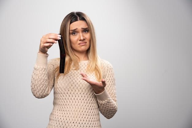 Rapariga loira verificando as fotos no rolo de fotos e se sentindo decepcionada.