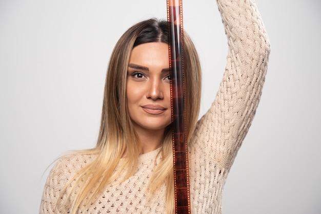 Rapariga loira verificando atentamente as fotos em filme polaroid