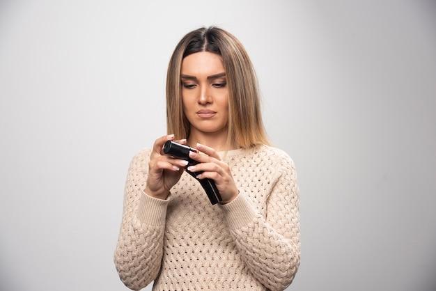 Rapariga loira verificando fotos em filme polaroid e se sentindo decepcionada