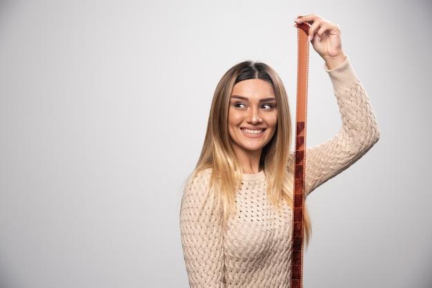 Rapariga loira verificando fotos em filme polaroid e se sentindo feliz e positiva com o resultado