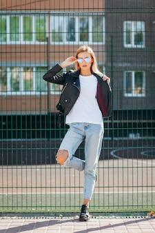 Rapariga loira vestindo camiseta, óculos e jaqueta de couro posando contra a rua
