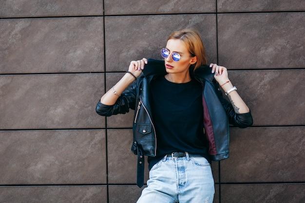 Rapariga loira vestindo camiseta preta, óculos e jaqueta de couro posando contra stree