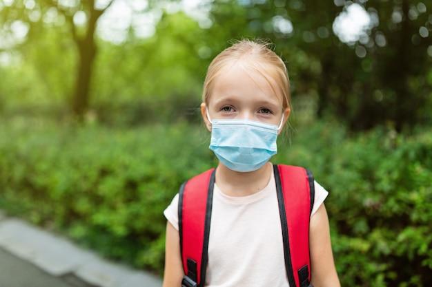 Rapariga loira voltando para a escola após quarentena e bloqueio covid-19