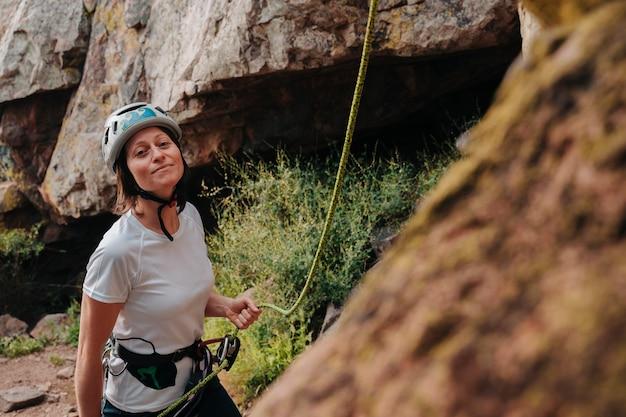 Rapariga na casa dos 30 anos a preparar-se para escalar uma montanha