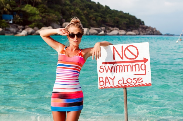Rapariga na praia com poster proibida