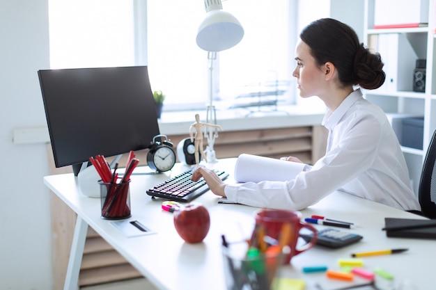 Rapariga no escritório trabalhando com documentos no computador.
