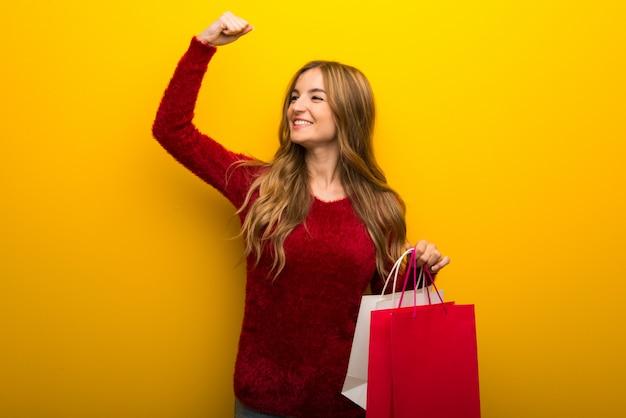 Rapariga no fundo amarelo vibrante segurando um monte de sacos de compras em posição de vitória