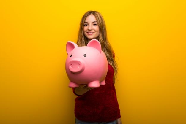 Rapariga no fundo amarelo vibrante segurando um piggybank
