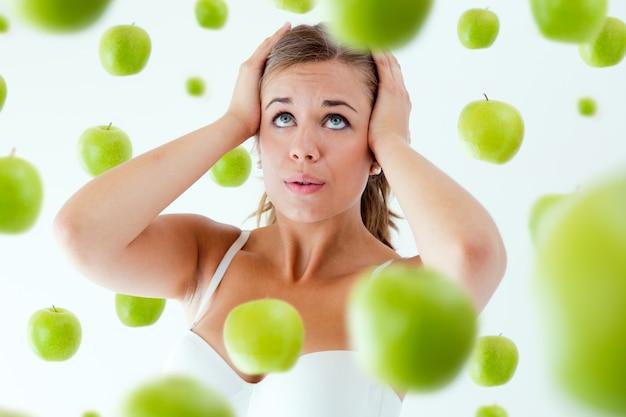Rapariga oprimida pela dieta, cercada por maçãs.