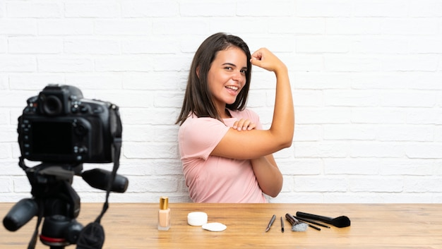 Rapariga que grava um tutorial em vídeo, fazendo um gesto forte