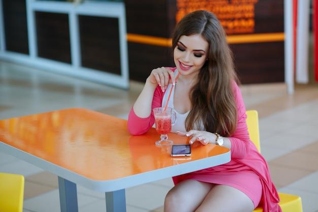 Rapariga que levanta com um telefone e um refrigerante