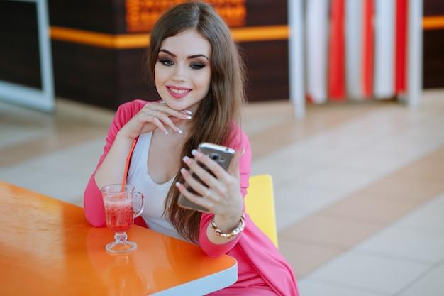 Rapariga que olha seu telefone e sorrindo