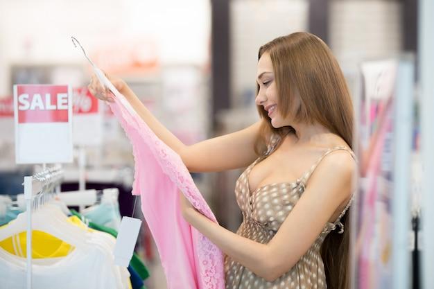 Rapariga que olha um vestido rosa Foto Premium