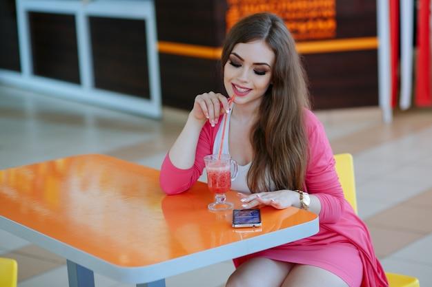 Rapariga que tem um refrigerante enquanto olha para seu telefone e sorrindo