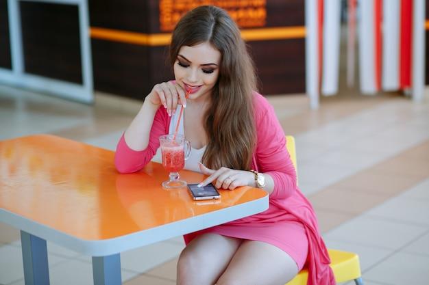 Rapariga que tem um refrigerante enquanto olha para seu telefone
