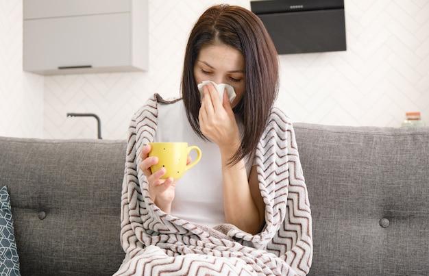Rapariga resfriada sentada no sofá em casa assoando o nariz