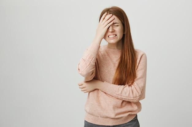 Rapariga ruiva angustiada na palma da mão, sentindo-se frustrada