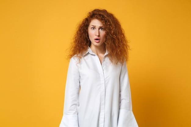 Rapariga ruiva chocada com uma camisa branca casual posando isolada em uma parede amarelo-laranja