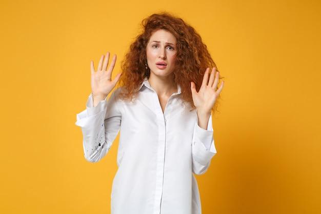 Rapariga ruiva chocada e descontente em uma camisa branca casual posando isolada em uma parede amarelo-laranja