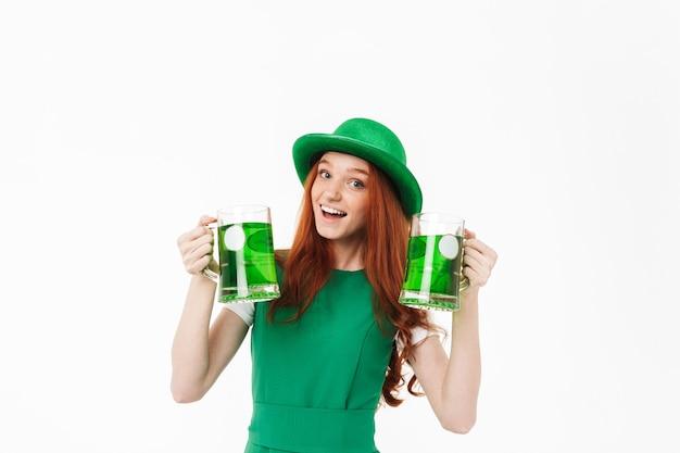 Rapariga ruiva feliz de chapéu verde, comemorando o dia de são patrício, isolada em uma parede branca, bebendo cerveja