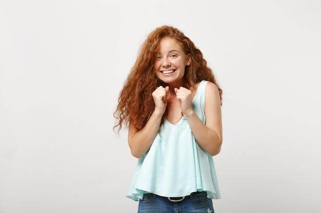 Rapariga ruiva muito alegre jovem em roupas leves casuais posando isolado no retrato de estúdio de fundo de parede branca. conceito de estilo de vida de emoções sinceras de pessoas. simule o espaço da cópia. cerrando os punhos.