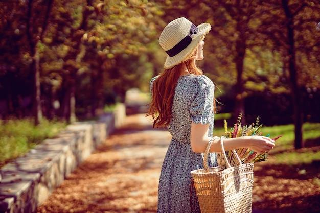 Rapariga ruiva passeando no parque no verão indiano, olhando para a estrada usando um vestido esvoaçante