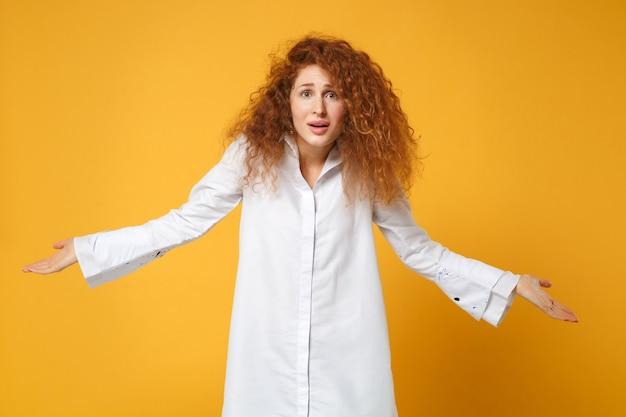 Rapariga ruiva perplexa em uma camisa branca casual posando isolada em uma parede amarelo-laranja Foto gratuita