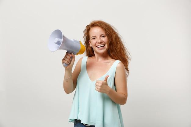 Rapariga ruiva sorridente jovem em roupas leves casuais posando isolado no fundo da parede branca, retrato de estúdio. conceito de estilo de vida de pessoas. simule o espaço da cópia. grite no megafone, aparecendo o polegar.