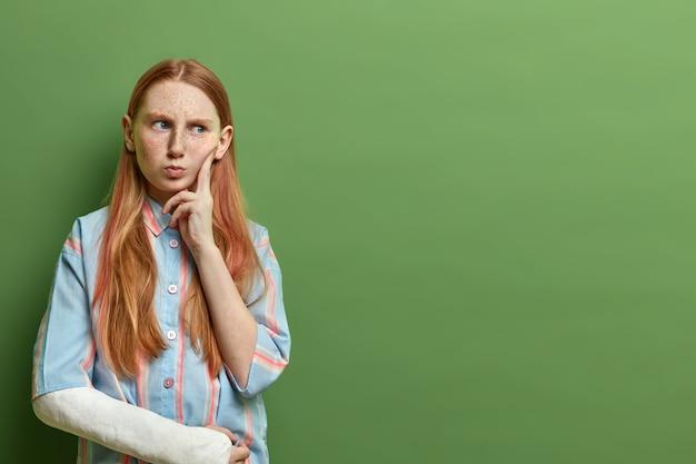 Rapariga ruiva taciturna tem rosto taciturno e zangado pensativo, mantém o dedo no rosto, pondera profundamente sobre algo importante, desvia o olhar, braço ferido engessado, isolado na parede verde, espaço vazio para promoção
