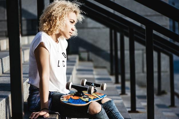 Rapariga sentada na escada com o skate