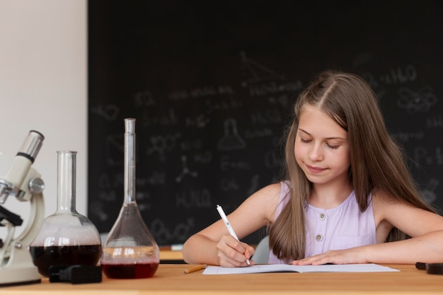 Rapariga sorridente a aprender mais sobre química na aula