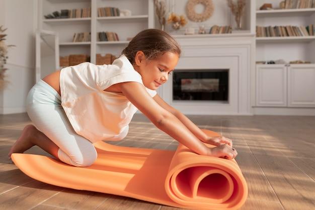 Rapariga sorridente com tapete de ioga