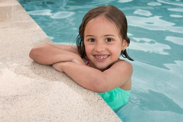 Rapariga sorridente com tiro médio a posar na piscina
