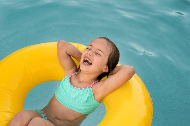 Rapariga sorridente com tiro médio e bóia salva-vidas