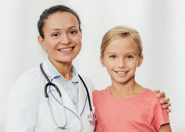 Rapariga sorridente com tiro médio e médico posando