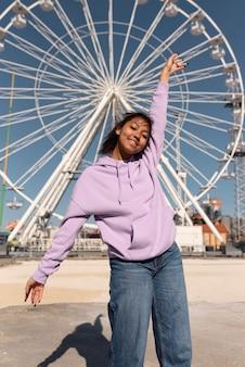 Rapariga sorridente com tiro médio no parque de diversões