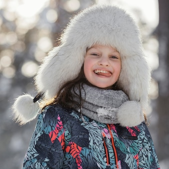 Rapariga sorridente com tiro médio usando chapéu