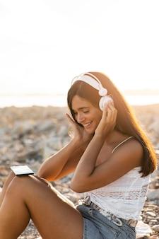 Rapariga sorridente com tiro médio usando fones de ouvido