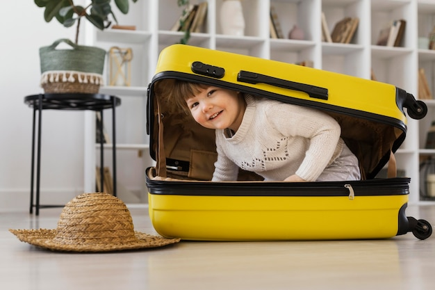 Rapariga sorridente de tiro completo sentada na bagagem