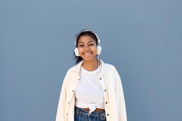 Rapariga sorridente de tiro médio com fones de ouvido