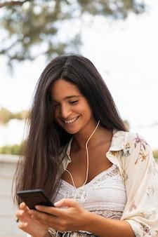 Rapariga sorridente de tiro médio com smartphone