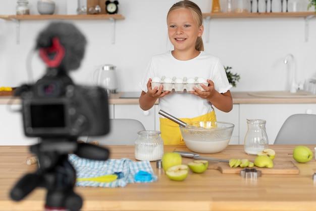Rapariga sorridente de tiro médio cozinhando