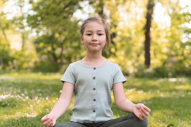 Rapariga sorridente de tiro médio meditando