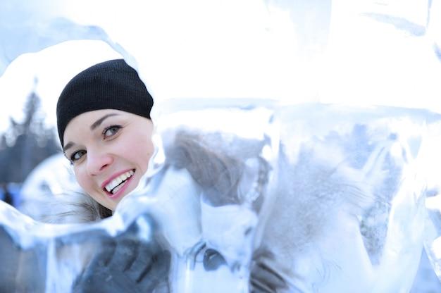 Rapariga sorridente olhando através de um buraco no gelo