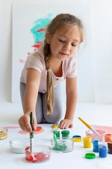 Rapariga sorridente pintando com pincel