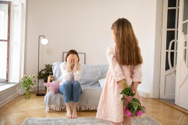 Rapariga surpreendendo mãe com flores tiro médio