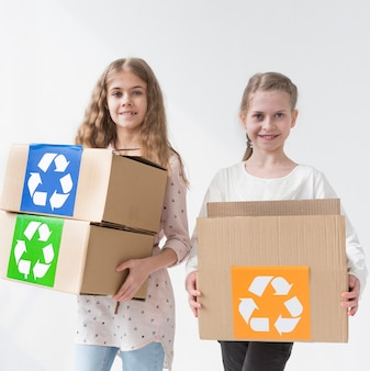 Raparigas felizes segurando caixas de reciclagem