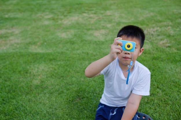 Rapaz a fotografar a câmara na relva