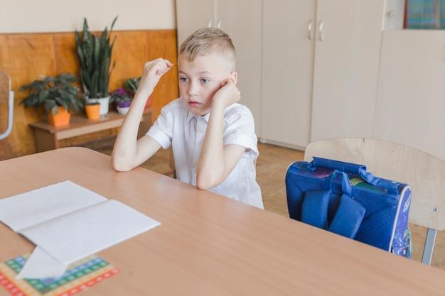 Rapaz a pensar durante a aula